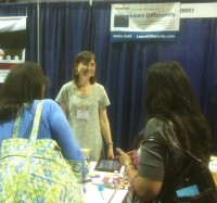 Kathy Kuhl with parents at her convention booth, where parents sometimes find new friends.